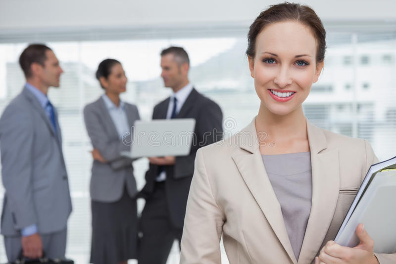 Cheerful businesswoman holding files smiling at camera royalty free stock image