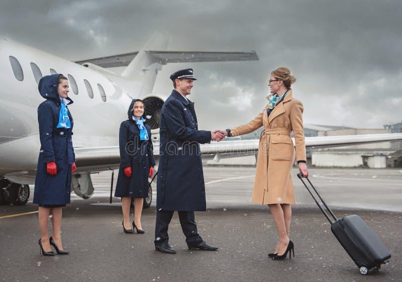 Cheerful businesswoman shaking hands aviator near plane royalty free stock photo