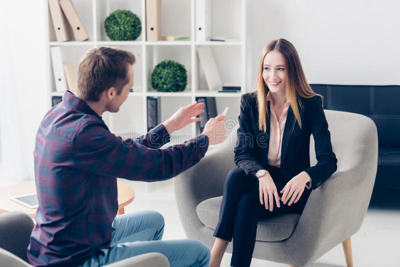 Cheerful businesswoman in suit giving interview to journalist. In office royalty free stock photos