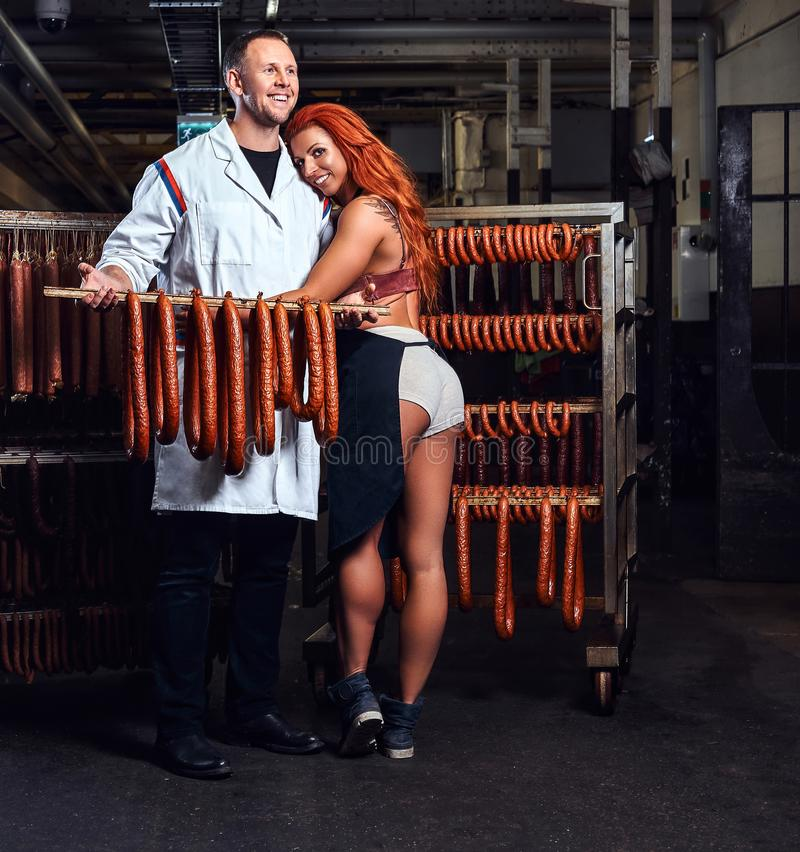 Cheerful butcher and his girl assistant in the storage room. stock photo