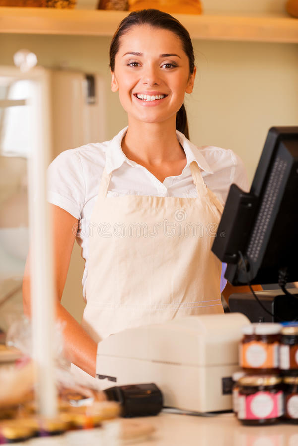 Cheerful cashier. Beautiful young female cashier in apron standing near cash register and smiling royalty free stock photography