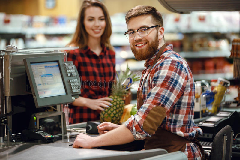 Cheerful cashier man on workspace in supermarket shop. Image of cheerful cashier men on workspace in supermarket shop. Looking at camera royalty free stock photography