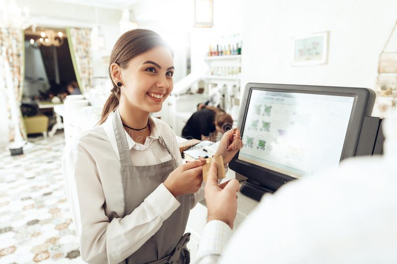 Cheerful cashier using digital device for payment stock photography