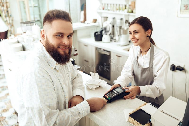Cheerful cashier using digital device for payment stock photo