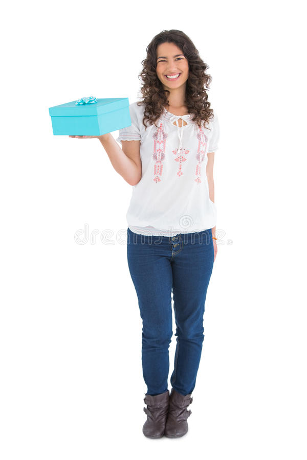 Cheerful casual brunette holding a present royalty free stock photo