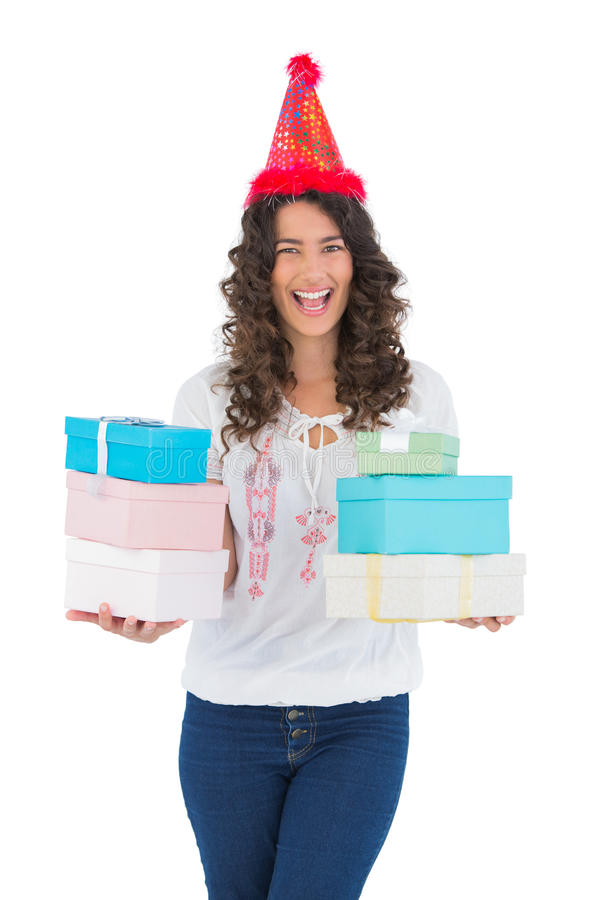 Cheerful casual brunette with party hat holding presents royalty free stock images
