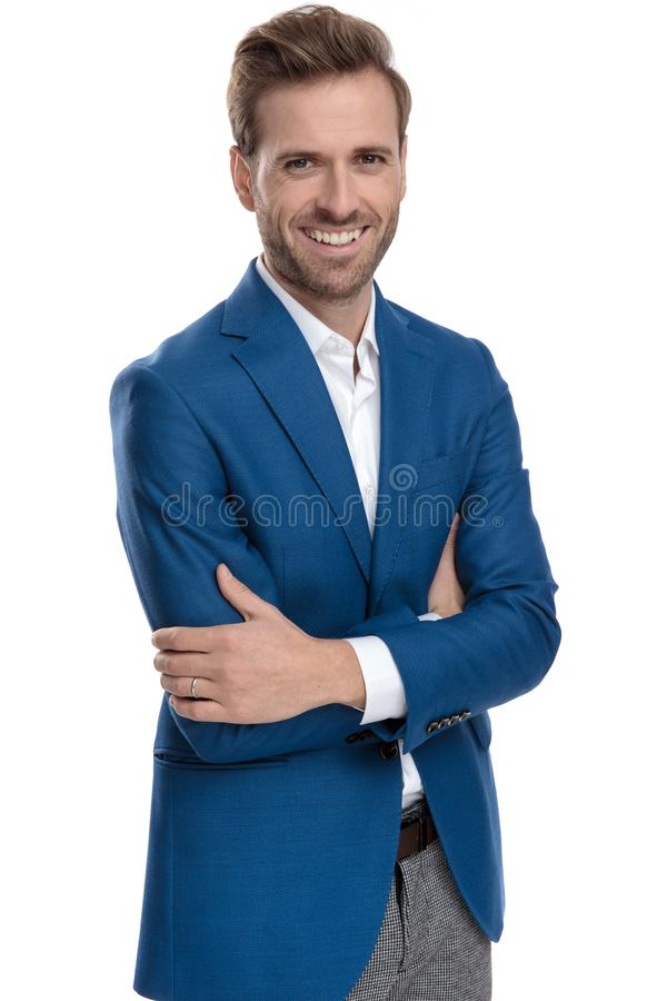 Cheerful casual guy holding his arms folded and laughing. Cheerful casual guy holding his arms folded at his chest and laughing while wearing a suit and standing stock images