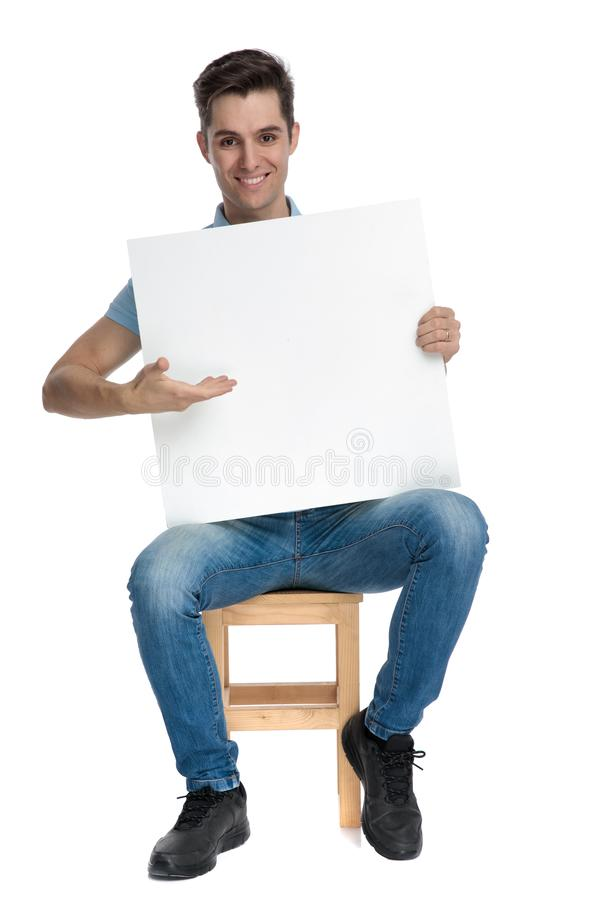 Cheerful casual guy presenting and empty billboard. While smiling and wearing blue jeans, sitting on a chair on white studio backgorund stock photos