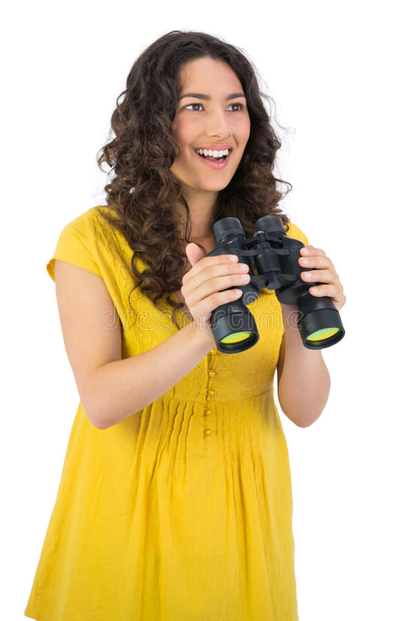 Cheerful casual young woman holding binoculars stock photo
