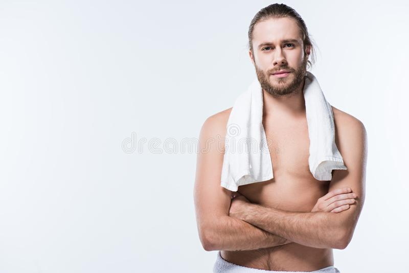 Cheerful caucasian man with bath towel around his neck looking at camera with arms crossed, royalty free stock images