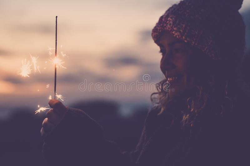 Cheerful caucasian woman with winter hat celebrate outdoor with fire sparkler - new year eve and event- happiness for alternative stock photo