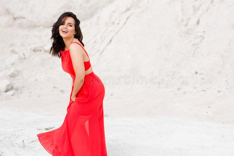 Cheerful charismatic girl in red dress with bare shoulders, poses outside in wilderness. Smiling young woman wearing the bright red dress looking at camera royalty free stock photo