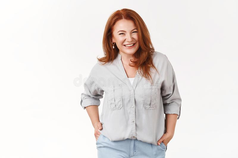 Cheerful charismatic middle-aged redhead beautiful woman smiling toothy happy hold hands pockets pleasant nice stock photo