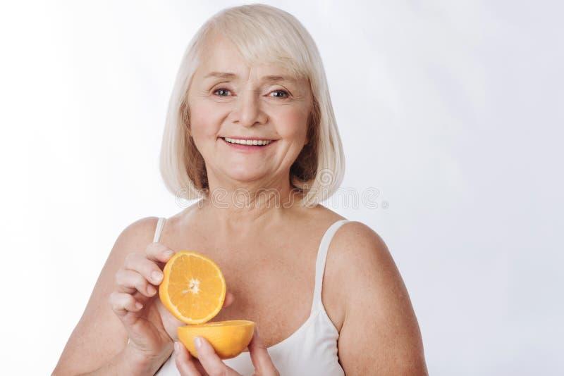 Cheerful charming woman using orange halves in cosmetics stock image