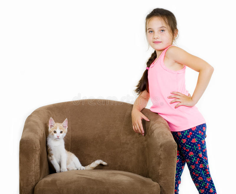 Cheerful cheerful child girl plays with a little kitten on a light background stock photos