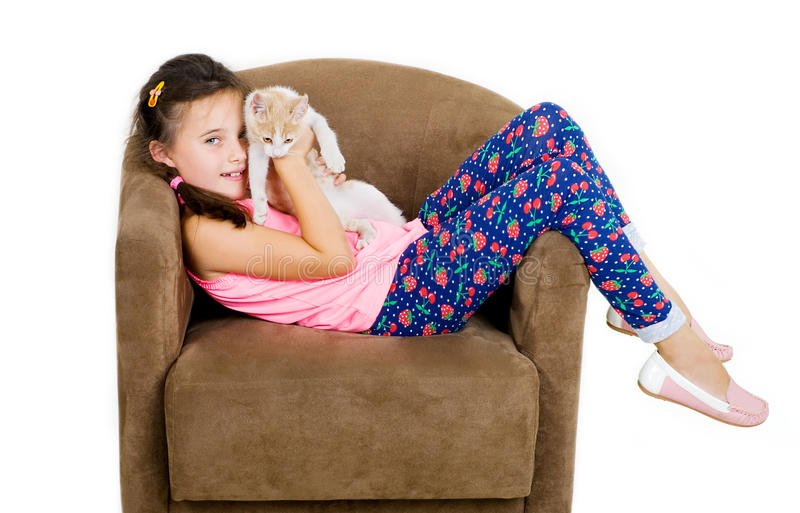 Cheerful cheerful child girl plays with a little kitten on a light background stock images