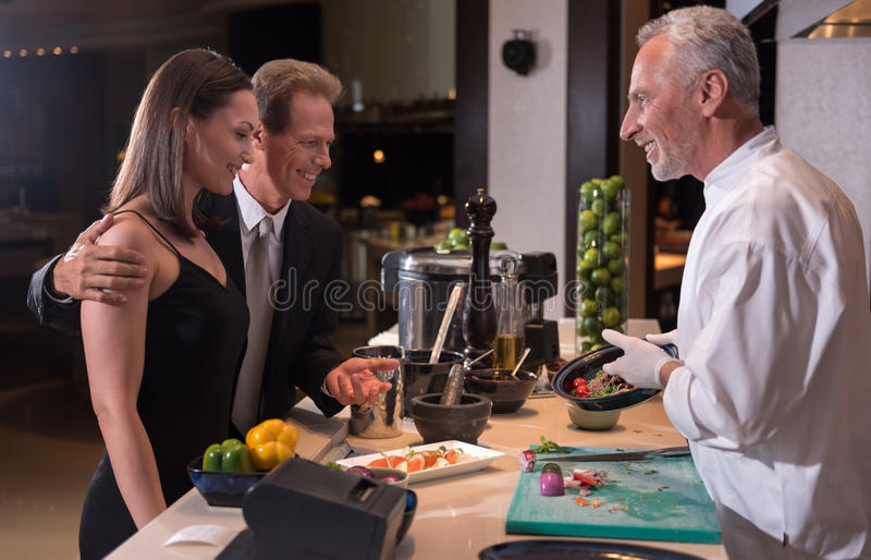 Cheerful chef advising the dish to the couple. Would you like to taste. Cheerful smiling bearded chef holding the plate with the dish and pointing on it while stock photography