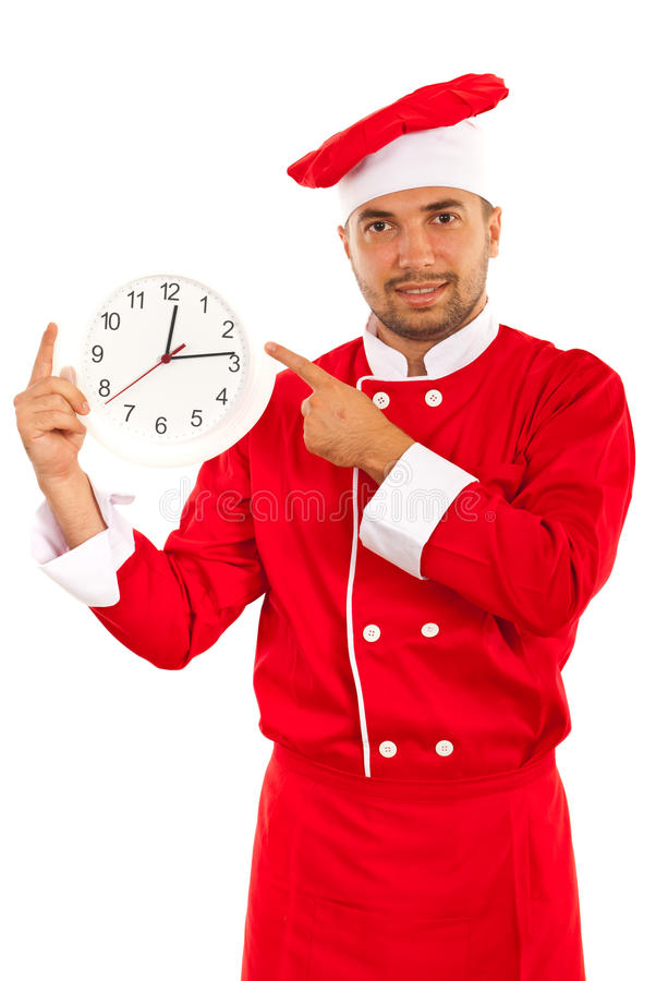Cheerful chef with clock. Cheerful chef in red uniform pointing to clocl isolated on white background stock image