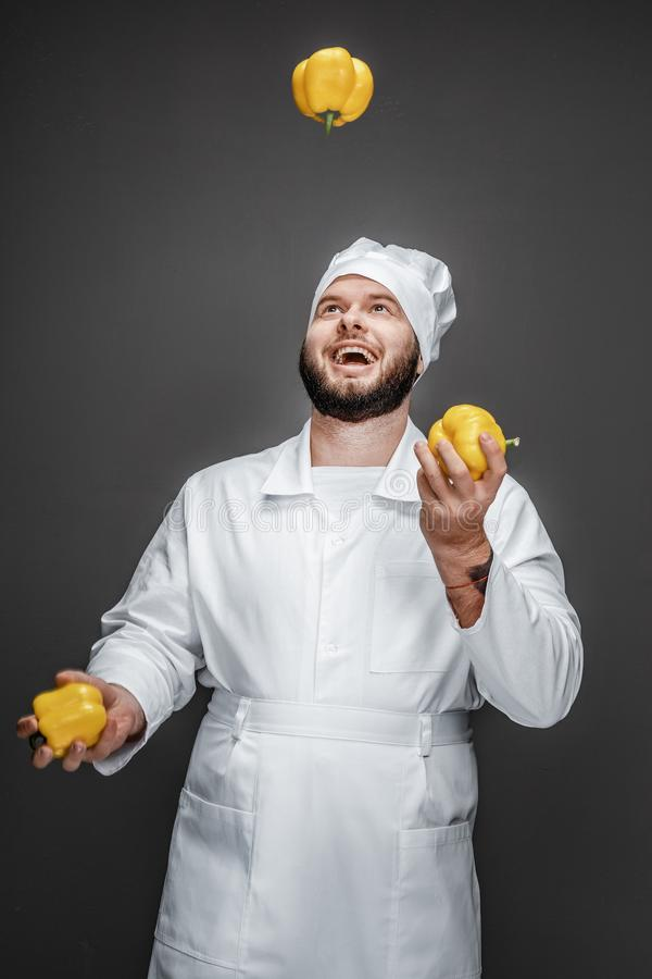 Cheerful chef juggling with ripe peppers stock image