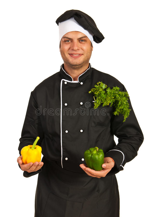 Cheerful chef showing bell peppers royalty free stock photos