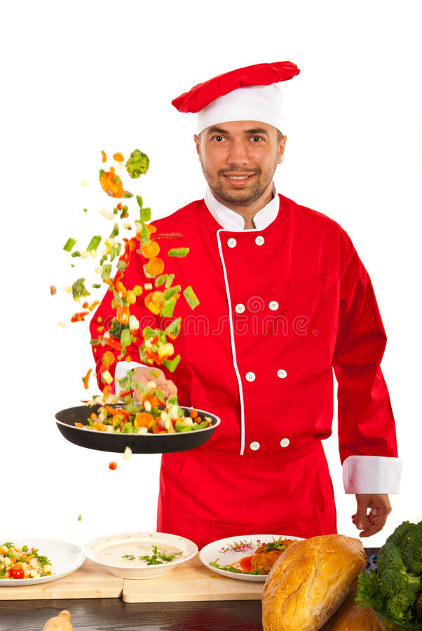 Cheerful chef tossing vegetables. In kitchen against white royalty free stock photography