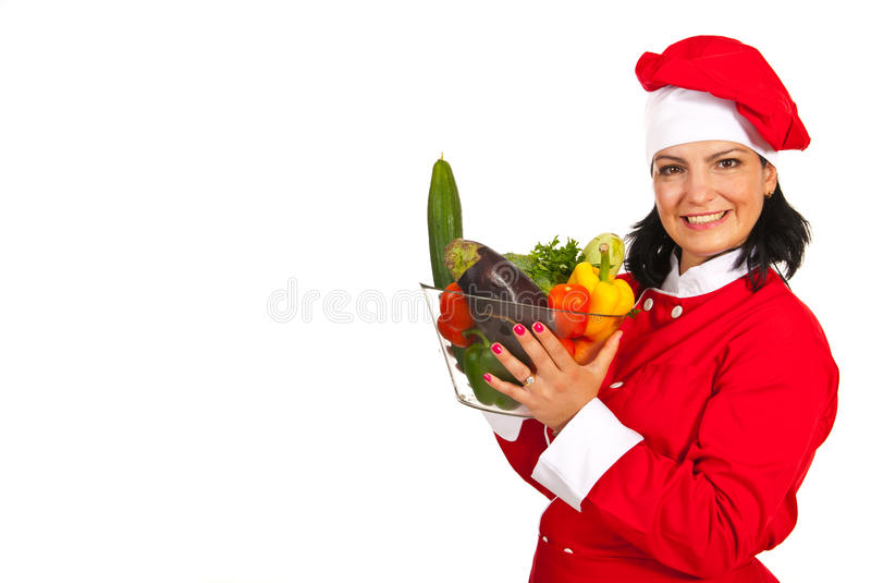 Cheerful chef woman holding vegetables stock photography
