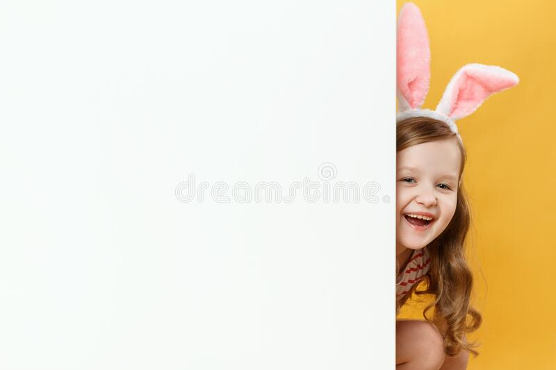 A cheerful child in the Easter bunny ears peeps out from behind a blank white banner. Little girl on a yellow background stock images