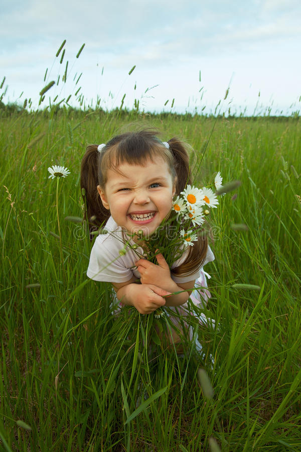 Cheerful child embraces wild flowers stock photos
