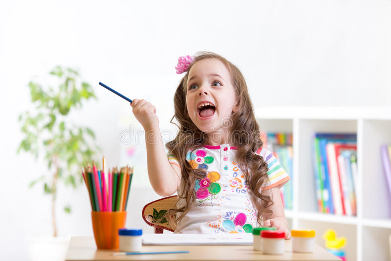 Cheerful child girl drawing with pencils in stock images