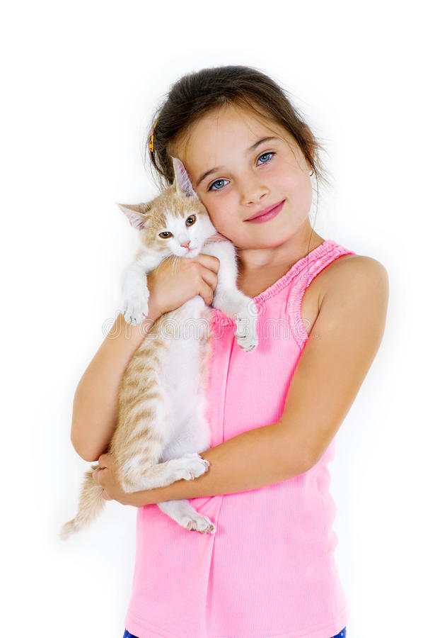 Cheerful child girl plays with a little kitten on a light background royalty free stock photos
