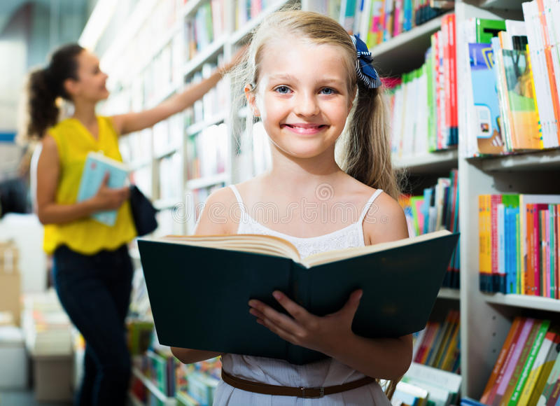 Cheerful child in school age shopping book. In bookstore royalty free stock photos