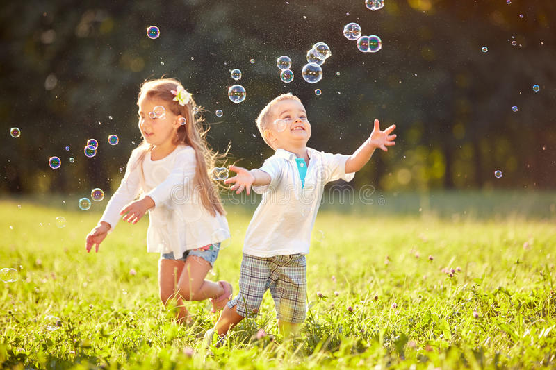 Cheerful children chase bubbles stock photo