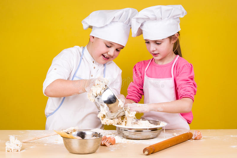 Cheerful children cook pizza. On the yelow royalty free stock photography