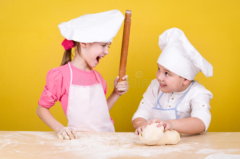 Cheerful children cook pizza. On the yelow stock images