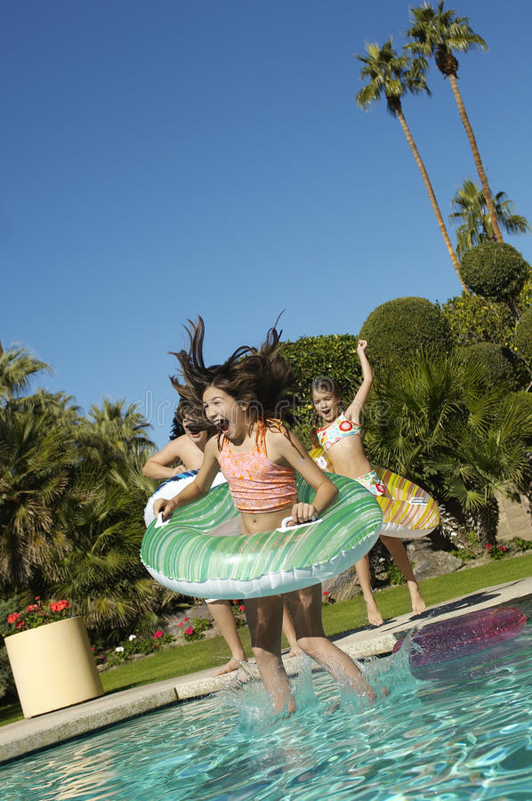 Cheerful Children Jumping Into Swimming Pool stock photo