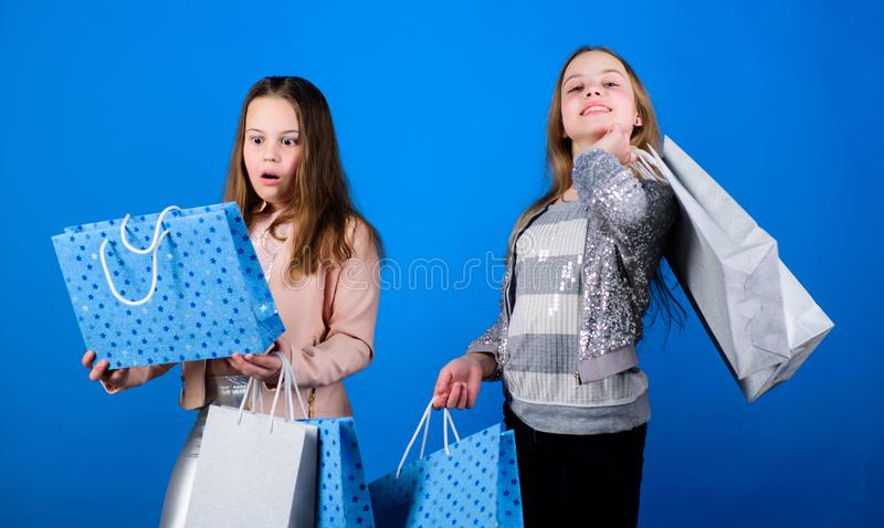 Cheerful children. Little girl sisters. Sisterhood and family. savings on purchases. Kid fashion. Blue background. Sales. And discounts. Small girls with stock photo