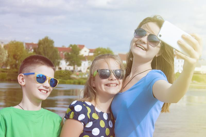 Cheerful children`s company makes selfie on a smartphone on a city street outdoor. stock photo
