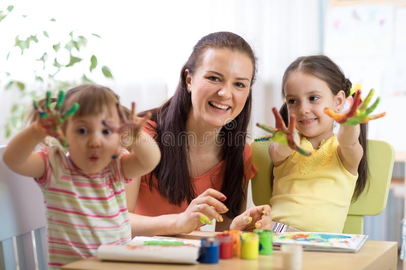 Cheerful children and their mother having fun and showing hands painted in colorful paints stock photo
