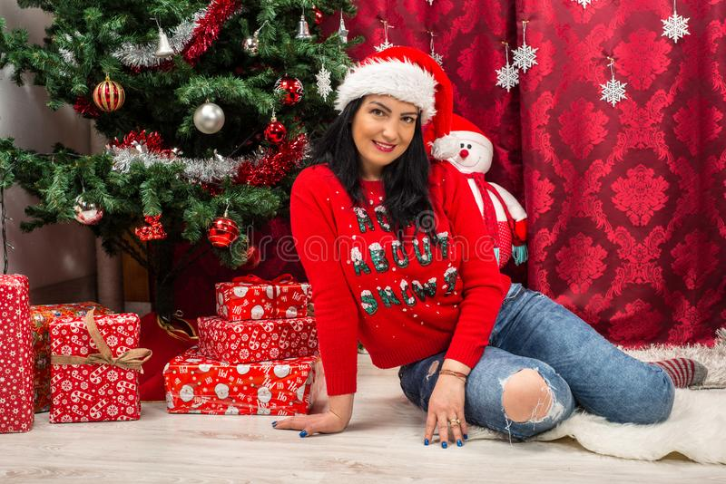 Cheerful Christmas woman. Sitting on floor near tree with presents stock image