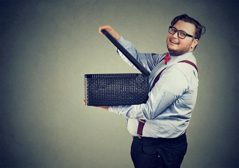 Cheerful chunky man opening a box. Side view of happy chubby man in glasses opening box releasing gifts and smiling at camera on gray royalty free stock photo