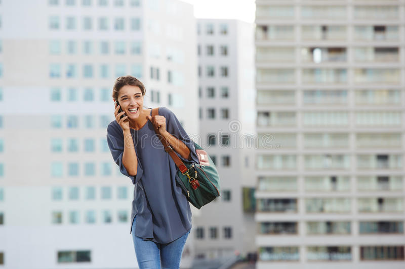 Cheerful city woman talking on mobile phone. Portrait of cheerful young woman talking on mobile phone outdoors in city royalty free stock photography