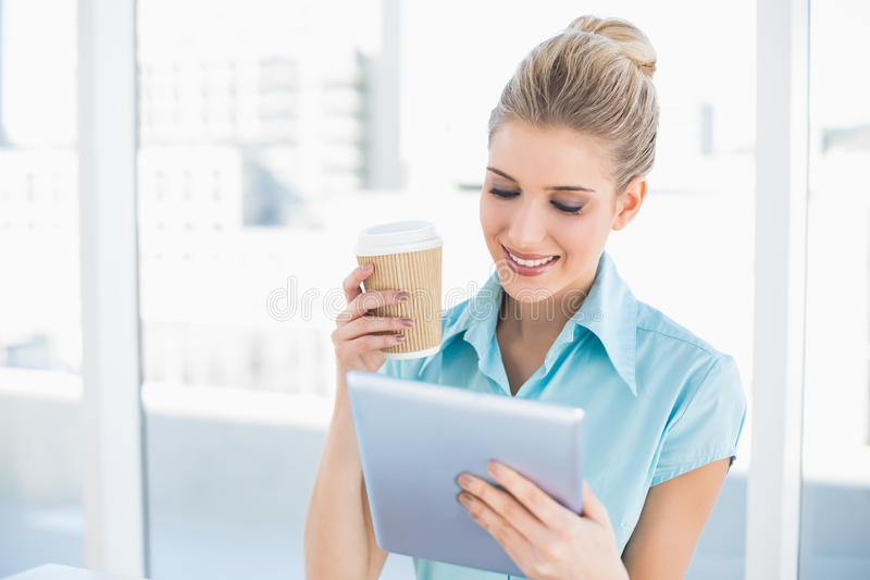 Cheerful classy woman using tablet holding coffee royalty free stock photography