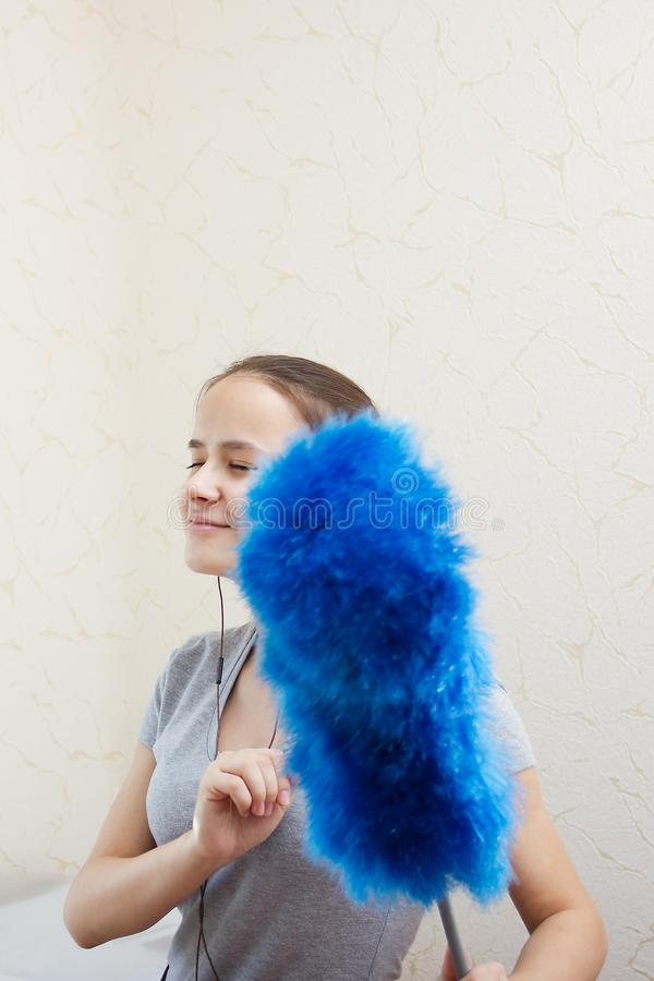Cheerful cleaning. Young European girl with long hair in a good. Mood in headphones is removed, listening to music and dancing at home royalty free stock images