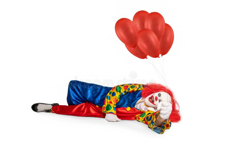 A cheerful clown lies on the floor holding balloons in his hand stock images