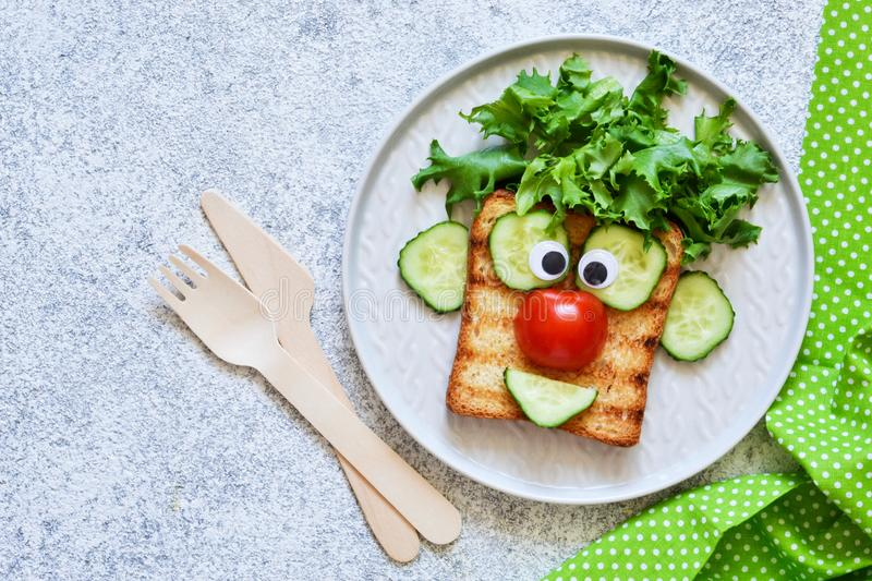 Cheerful clown. Sandwich for children for breakfast. View from above stock image