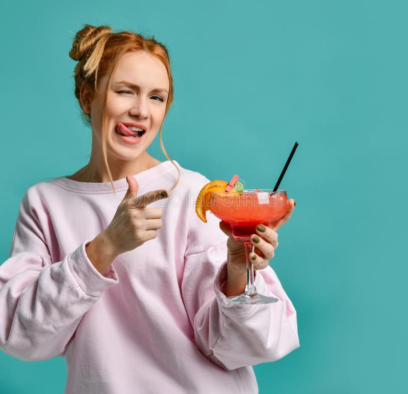 Cheerful clubbing young woman pointing her finger at the tropic cocktail strawberry margarita she holds and winks royalty free stock photography