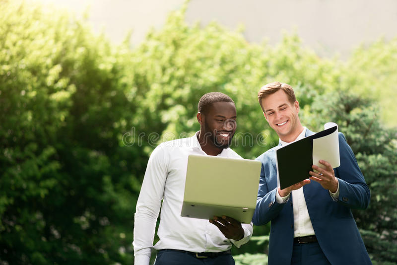 Cheerful colleagues discussing project. Express your ideas. Positive delighted smiling colleagues holding laptop and discussing project while standing outdoor stock images