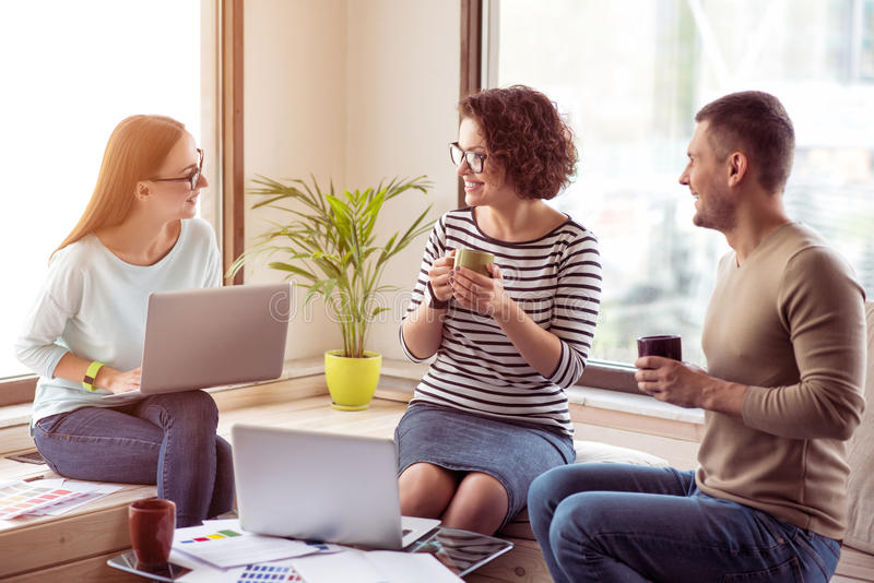 Cheerful colleagues drinking coffee in the office stock photo