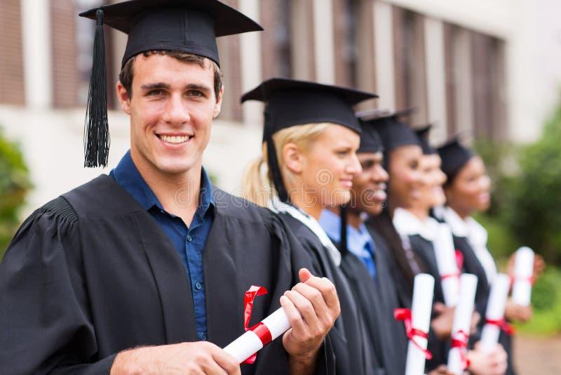 Cheerful college graduates. Portrait of group cheerful college graduates at graduation stock photo