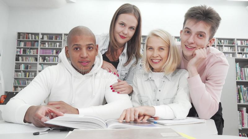Cheerful college students smiling to the camera while studying together royalty free stock photography